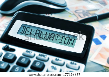 word devaluation on the display of a calculator with euro bills in the background - stock photo