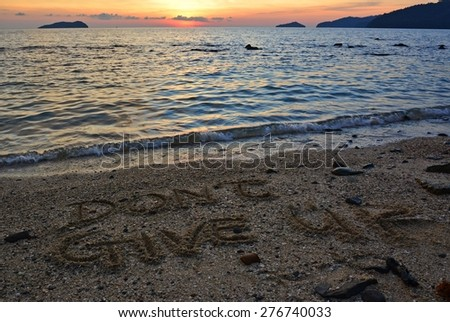 """Word """"Don't give up"""" handwritten in sand at beach during sunset - stock photo"""
