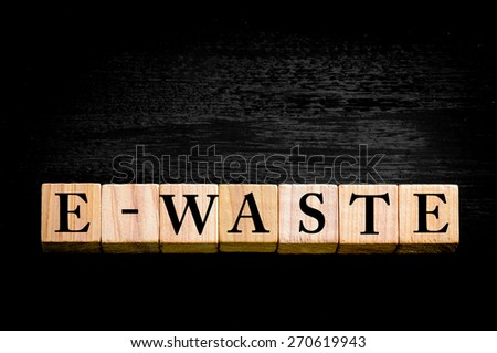 Word E-WASTE standing for ELECTRONIC WASTE. Wooden small cubes with letters isolated on black background with copy space available. Concept image. - stock photo