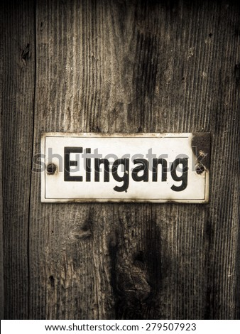 word entrance on wooden door - german eingang - stock photo