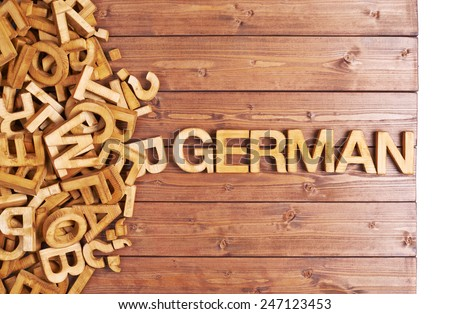 Word german made with block wooden letters next to a pile of other letters over the wooden board surface composition - stock photo