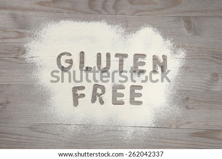 Word gluten free written in white flour on a old wooden table, vintage tone. - stock photo