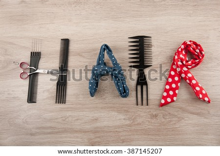 Word hair consist of hairdressing accessories laying on wooden table. Comb, Brush, scissors and colored ribbons - stock photo