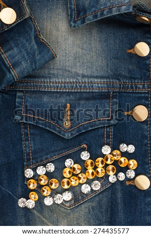 Word jeans made of rhinestones on denim jacket, as background - stock photo