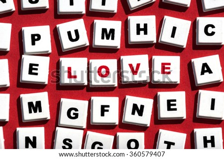 "Word letters spelling out the word ""Love"" on red paper background - stock photo"