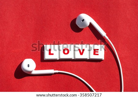 "Word letters spelling out the word ""Love""  with earphones on red paper background - stock photo"