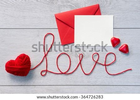 "Word ""love"" and red envelope with letter on a wooden background. Valentines Day background - stock photo"