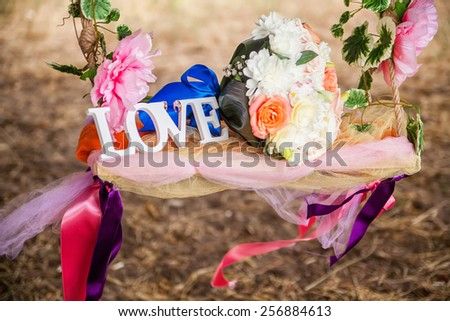 Word Love and wedding bouquet of flowers on a romantic floral swing as a Valentine's Day love or Wedding composition, background - stock photo