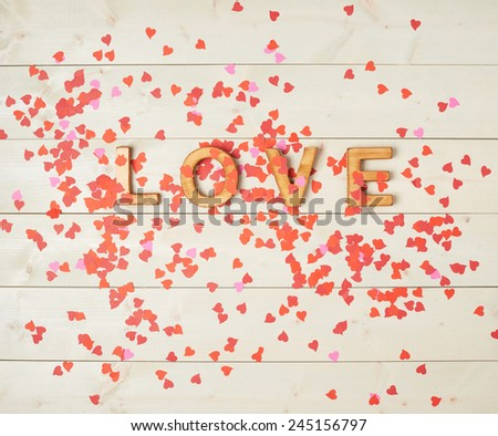 Word Love composition over the wooden board surface and covered with multiple heart shaped confetti - stock photo