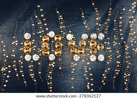 Word love made of rhinestones on denim fabric, as background, texture - stock photo