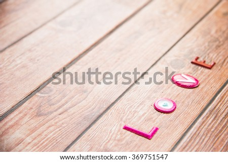 Word Love on wooden background.Sweet holiday,Happy Valentines day, wedding day, Mother's day, Anniversary for special person. Left space and text on right askew of frame. - stock photo