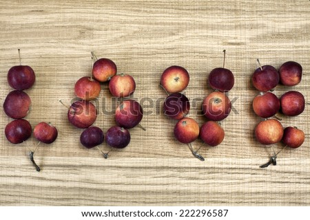 Word love with small red-ripe apples on wooden board. Sweet holiday background. Image of natural materials. Eco style.  - stock photo