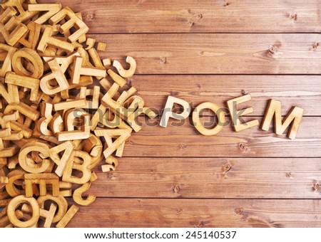 Word poem made with block wooden letters next to a pile of other letters over the wooden board surface composition - stock photo
