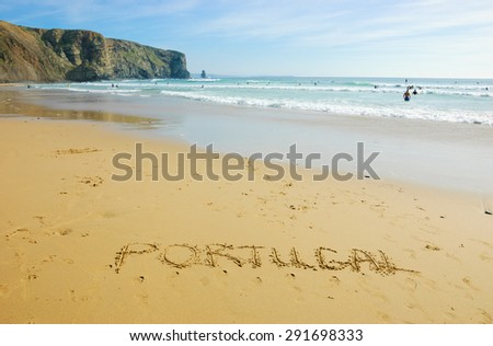 Word PORTUGAL is written on the scenic beach in the Algarve region of Portugal. People swimming and surfing.  - stock photo