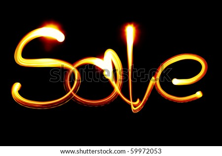 Word SALE created by light over black background - stock photo