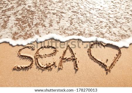 word sea on beach sand - stock photo