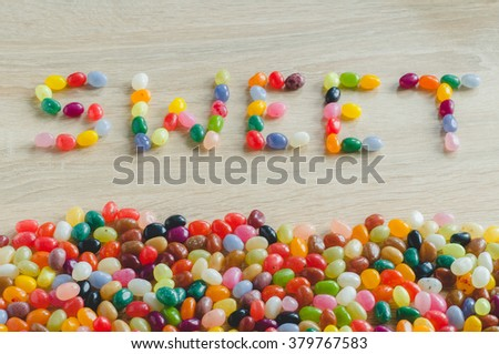 "Word ""sweet"" with border from jelly beans on wooden background - stock photo"