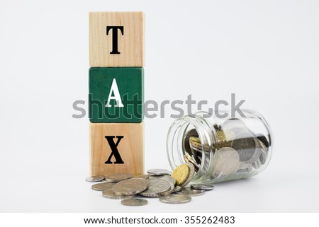 Word Tax on wooden block with coins in glass jar - stock photo