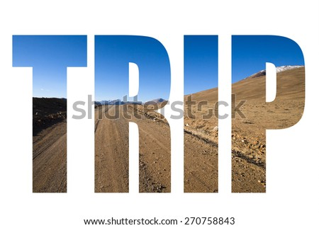 Word TRIP over beautiful landscape - country road in desert valley. The rocky mountains and blue sky are behind. Toned - stock photo