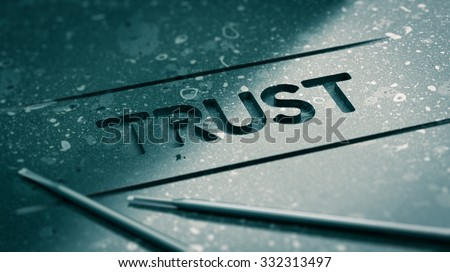 Word trust engraved in black stone with tools and blur effect. Concept image for illustration of strong relationship or partnership and faith.  - stock photo