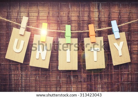 word unity  design by white letterpress with box paper hang on rope by wooden peg over metal net and brown wooden background, vignette effect. - stock photo