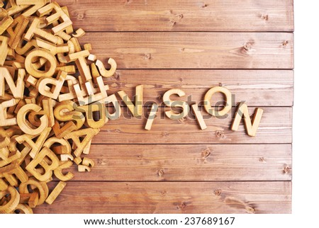 Word vision made with block wooden letters next to a pile of other letters over the wooden board surface composition - stock photo