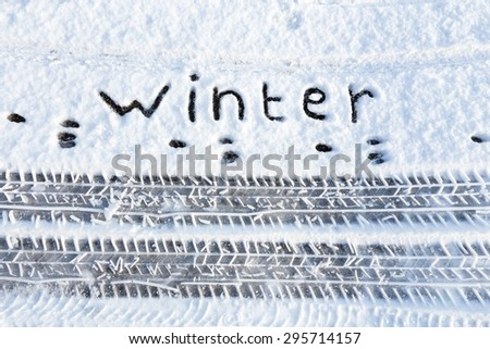 Word winter and tire tracks in snow - stock photo