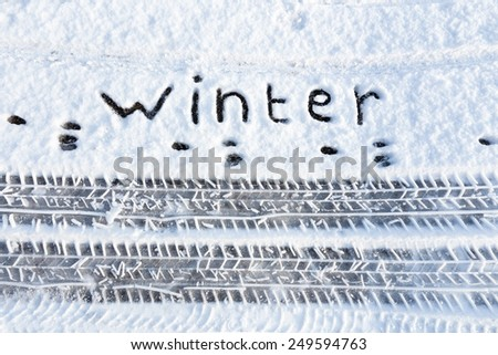Word winter and tire tracks in snow on road - stock photo