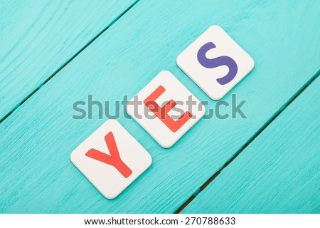 Word yes on blue wooden background - stock photo