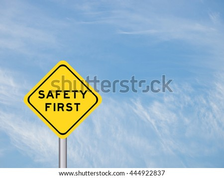 "wording ""Safety first"" on yellow traffic sign with pole on the blue sky - stock photo"