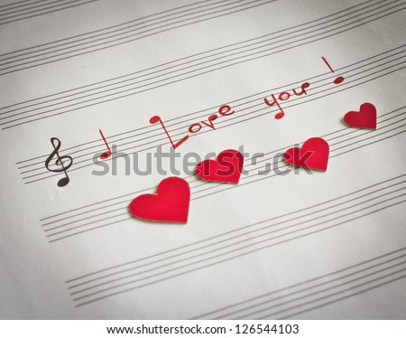 "Words ""I love you !"" in shape of music notes in the music note book with red hearts - stock photo"