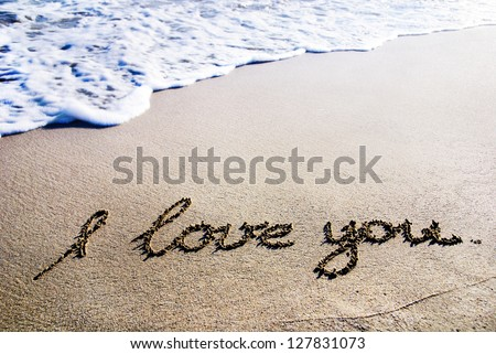 """words """"I love you"""" outline on the wet sand with the wave brilliance - stock photo"""