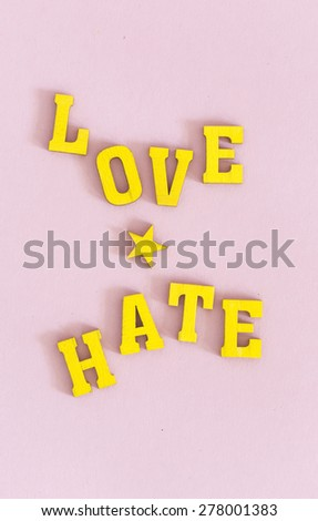 "Words ""love"" and ""hate"" in yellow wooden letters on pink background  - stock photo"