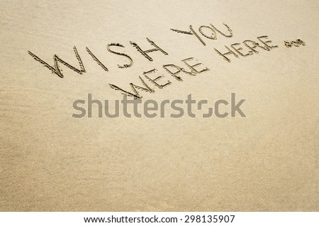 Words wish you were here written in the sand on the beach. - stock photo