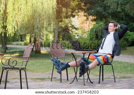 Work and relax outdoor. Businessman dressed in suit, shorts and rollers working with laptop at the park cafe - stock photo
