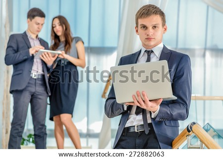 Work at lunch . Young and successful businessman standing on the stairs holding a laptop and smiling and looking into the camera in the meantime there are two people in the background. - stock photo
