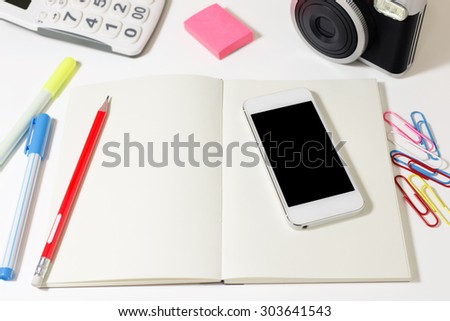 Work desk with blank notebook, phone, camera, calculator and pencil - stock photo