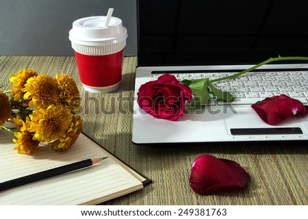 Work desk with red rose and cup of coffee - stock photo
