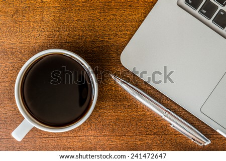 Work in the office, coffee cup with laptop and a pen on the wooden table - stock photo