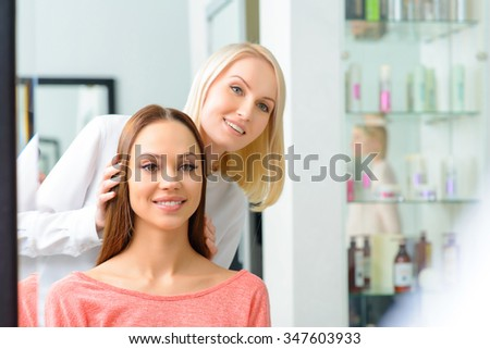 Work is done. Appealing professional is showing the front of brand new hairdo to her client. - stock photo