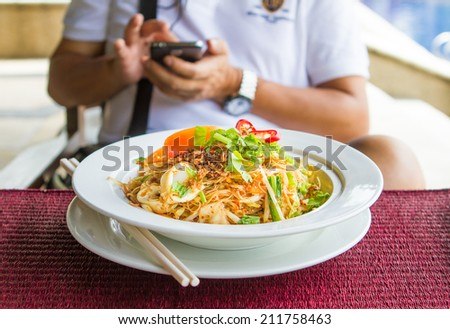 Work on the phone while having stir-fry noodles - stock photo