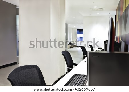Work place with computers, monitors and chairs with a room inside illuminated using lights - stock photo
