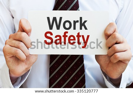 Work Safety. Man holding a card with a message text written on it. Man holding a card with a message text written on it - stock photo