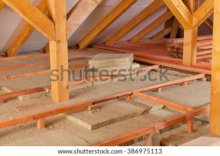 Work site of installing thermal insulation under the roof - mineral wool panels and wooden planks - stock photo