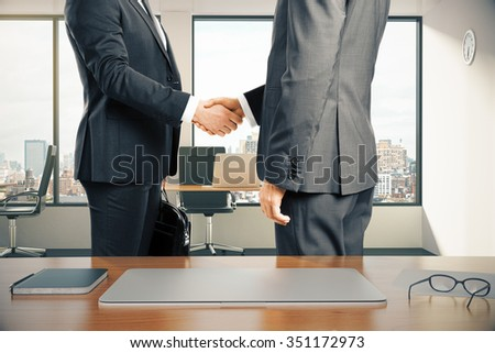 Work space with laptop and businessmen shaking hands in modern office - stock photo