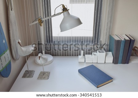 work table with lamp,pencils and books in working room - stock photo