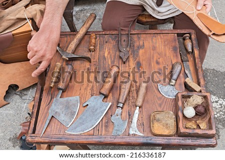 work table with old tools of the artisan shoemaker for cutting and sewing the leather - reenactment of ancient medieval work  - stock photo