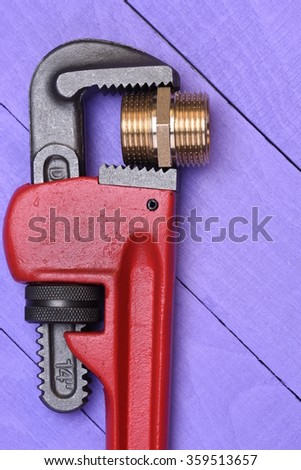 Work tool wrench and brass plumbing part on wooden background  - stock photo