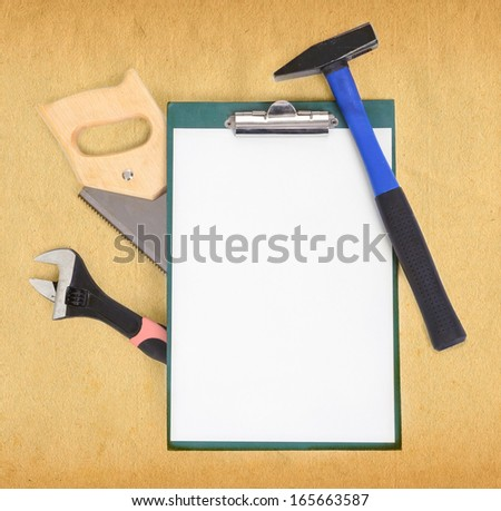 Work tools and clipboard over rough brown paper background - stock photo