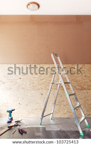 Work tools and ladder in front of new blank unfinished wall made of plywood - stock photo